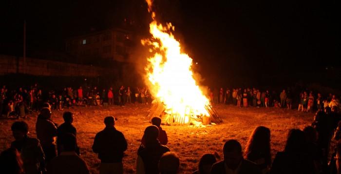 Photo d'un feu de joie avec de nombreux jeunes se tenant autour