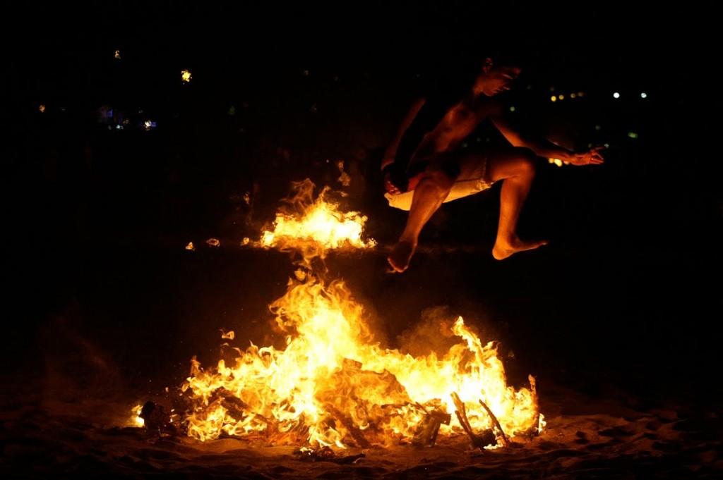 Photo d'un jeune homme sautant au dessus d'un feu de joie durant la nuit de la San Juan